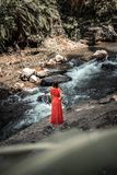 Young woman in long red dress posing on a mountain river deep in the rainforest of Bali island, Indonesia. royalty free stock photography