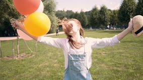 Smiling ginger woman in hat running to camera with balloons in park stock footage