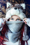 Young woman with long red hair wearing a fluffy wolf hat. Stock Images