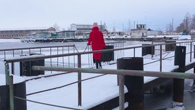 Young woman in long red jacket passes through snow-covered pier and looks into distance at frozen river in winter. Backside view young woman in long red jacket stock video footage