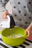 Young woman in long sleeve shirt with stars mixing and tasting dough for homemade muffins. Cooking and baking at home. Bright kitc stock photography