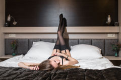 Young woman with long slim sexy legs in black lingerie Royalty Free Stock Photography