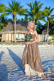 The young woman in a long sundress on a tropical beach. Stock Images