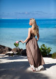 Young woman in a long sundress on a tropical beach. Polynesia. Stock Photography
