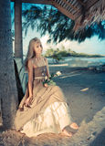 The young woman in a long sundress on a tropical beach. ,with a retro effect Royalty Free Stock Images