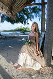 The young woman in a long sundress with a white rose in hands on a tropical beach. Polynesia. Island Stock Photo