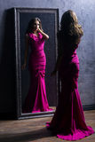 Young woman in a long violet dress next to a mirror Stock Image