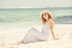 Young woman in long white dress and hat relaxing Stock Photos