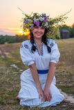 A young woman in a long white embroidered shirt and in a wreath. Of wild flowers sits in the field at sunset in the background an ancient flour mill. Girl in Royalty Free Stock Photos