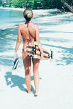 Young woman with longboard in hand walking on white sand Stock Photo