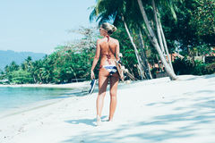 Young woman with longboard in hand walking on white sand Royalty Free Stock Photo