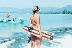 Young woman with longboard in hand walking on white sand Royalty Free Stock Image