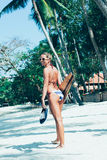 Young woman with longboard in hand walking on white sand Stock Photos