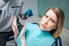 Young woman look afraid. She sit in chair in dentistry. Woman look on camera and push away doctor. He hold dentist`s. Young women look afraid. She sit in chair stock images