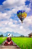Young woman look at balloon and sitting on wooden path with green rice field in Vang Vieng, Laos.  Stock Photos