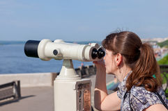 Young woman look in the coin operated binocular Royalty Free Stock Photos