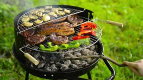 Outdoor grill with burgers, sausages, mushrooms and peppers stock video footage
