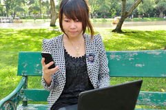 Young woman look at mobile phone with laptop Stock Photos