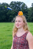 Young woman looking afraid at arrow in apple on head. Outdoors Royalty Free Stock Photography