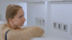 Young woman looking around in modern photo gallery stock video footage