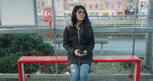 Young woman looking around and waiting for a bus at bus stop. Red Eoic 4k stock video footage