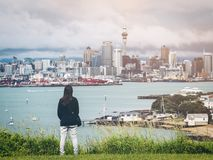 Young woman looking Auckland city skyline. Young woman looking at Auckland city skyline of city center and Auckland Sky Tower in New Zealand Stock Photo