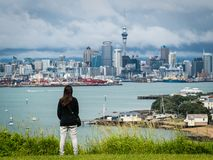 Young woman looking Auckland city skyline. Young woman looking at Auckland city skyline of city center and Auckland Sky Tower in New Zealand Royalty Free Stock Photography