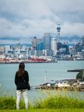 Young woman looking Auckland city skyline. Young woman looking at Auckland city skyline of city center and Auckland Sky Tower in New Zealand Royalty Free Stock Photo