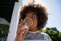Young woman looking away while drinking coffee Royalty Free Stock Image