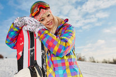 Young woman looking away while holding snowboard in snow Stock Photography
