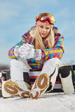 Young woman looking away while holding snowboard in snow Stock Images