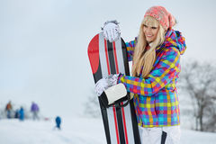 Young woman looking away while holding snowboard in snow Stock Photos