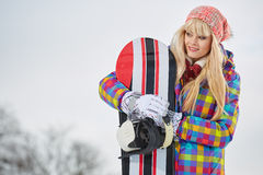 Young woman looking away while holding snowboard in snow Royalty Free Stock Image