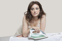 Young woman looking away while ironing shirt over gray background Stock Photos