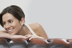 Young woman looking away while leaning on sofa against gray background Royalty Free Stock Images