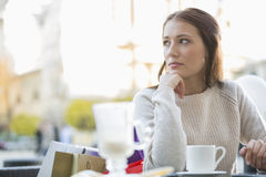 Young woman looking away while sitting at sidewalk cafe Royalty Free Stock Image
