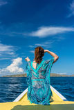 Young woman looking away to the horizon while sitting on a jetty. Rear view of a young woman looking away to the horizon while sitting on a jetty at seashore Royalty Free Stock Photography