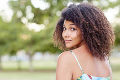 Young woman looking back over her shoulder in a park Royalty Free Stock Photo