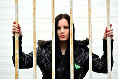 Young woman looking from behind the bars Stock Images