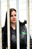 Young woman looking from behind the bars Stock Photo