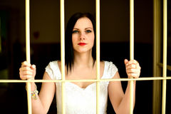 Young woman looking from behind the bars Royalty Free Stock Photos