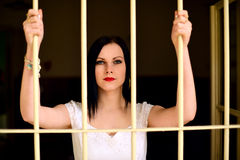 Young woman looking from behind the bars Royalty Free Stock Images