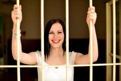 Young woman looking from behind the bars Royalty Free Stock Image