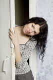 The young woman  looking from behind the door Royalty Free Stock Images