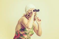 Young woman looking through a Binocular Royalty Free Stock Photos