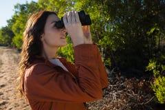 Woman looking through binocular by tree Royalty Free Stock Image