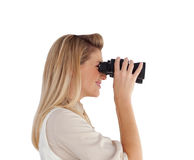 Young woman looking through binoculars Stock Photo