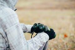 Young woman looking through binoculars on a autumn nature. Binoc. Ular, traveler, hiking.  young caucasian female hiker holding in his hand binoculars Royalty Free Stock Image
