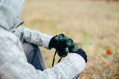 Young woman looking through binoculars on a autumn nature. Binoc Stock Photo