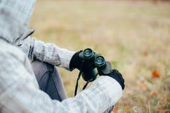 Young woman looking through binoculars on a autumn nature. Binoc. Ular, traveler, hiking.  young caucasian female hiker holding in his hand binoculars Stock Photo